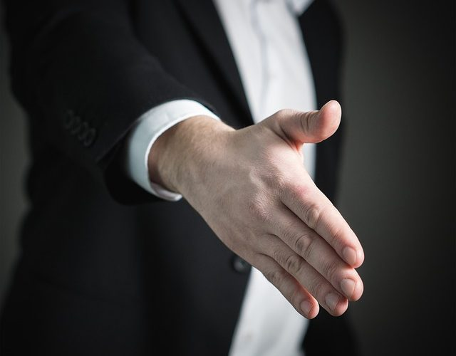 A man in a suit offering a handshake.