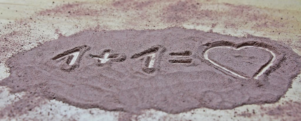 one plus one equals love written in sand.