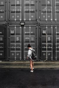 A girl with a backpack in front of large black storage containers