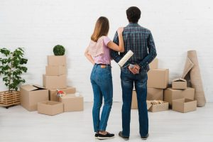 A couple packing for a move after finding affordable moving services.