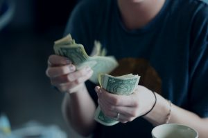 woman in blue shirt counting dollar bills