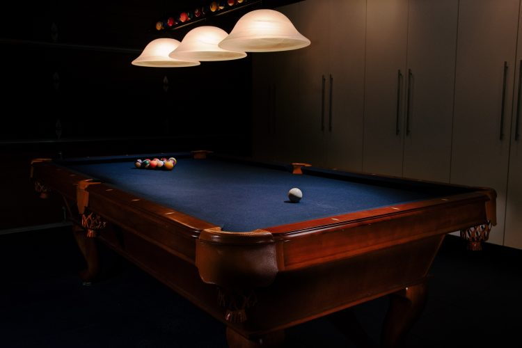 blue felt pool table under a dim light