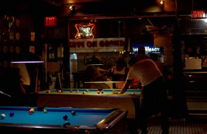 people playing pool in dim light