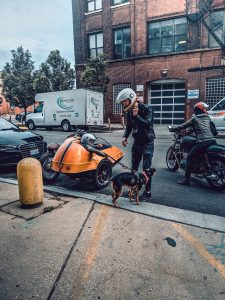 man standing next to a motorcycle with a dog