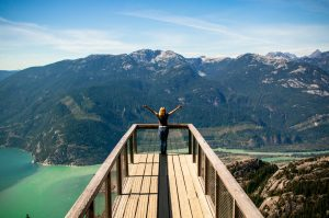Person in wooden balcony overlooking mountains