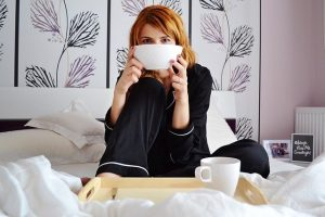 A woman enjoying her breakfast in bed after settling down in Florida