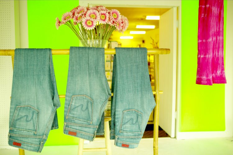 three pairs of jeans in a wardrobe