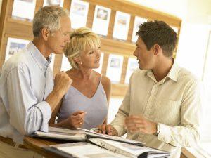 an elderly couple consulting with the moving expert about the value of the move