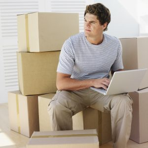 a man using his laptop to calculate how much do full service movers cost before moving