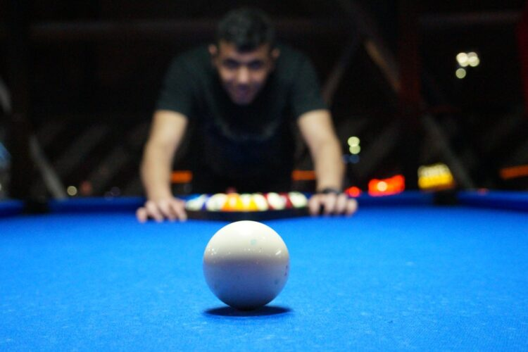Man playing a game of pool before he finds out about the cost of moving a pool table