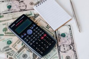 a calculator and a notepad on a stack of money you can save by moving in off peak season