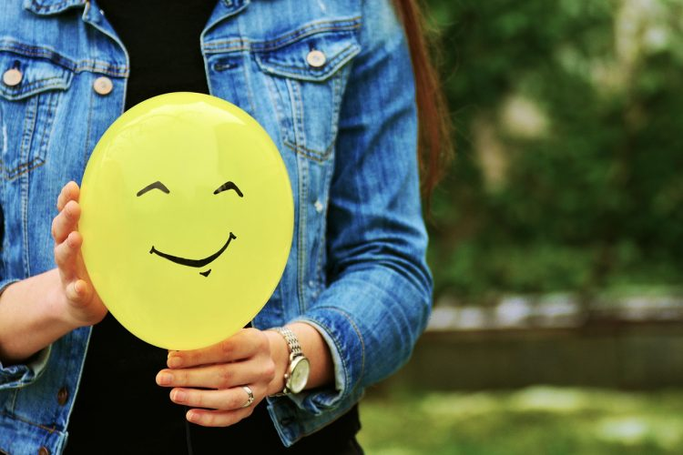 a girl holding a baloon