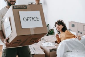 a couple carying boxes in order to learn how to choose moving services you need